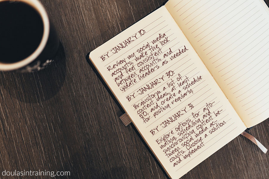 Notebook open with smart goals for social media written on it. Goals are the same web site goals as in the text below.