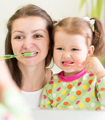 Woman and child brushing teeth together