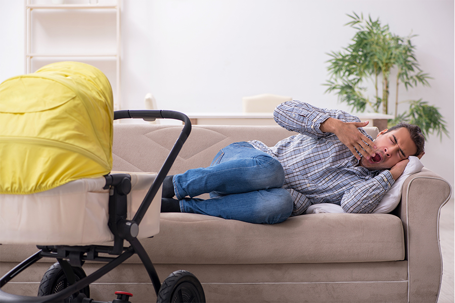 Man laying on the couch yawning, with stroller nearby